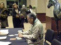 <h2>Autographing CDs For Some Fans 6 </h2><p>Janet Quigg, in a black coat, watches R. Carlos Nakai autograph a CD for a fan<br></p>