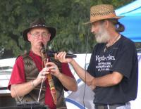 <h2>Robert Mullinax 1 </h2><p>Robert Mullinax  playing Native American flute while event staff member holds the microphone for the performance. <br></p>