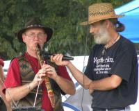 <h2>Robert Mullinax 2 </h2><p>Robert Mullinax  playing Native American flute while event staff member holds the microphone for the performance. <br></p>